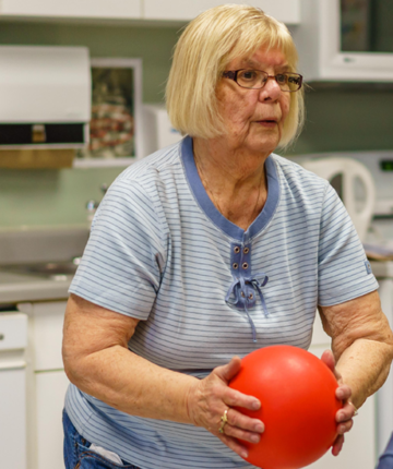 senior woman holding ball